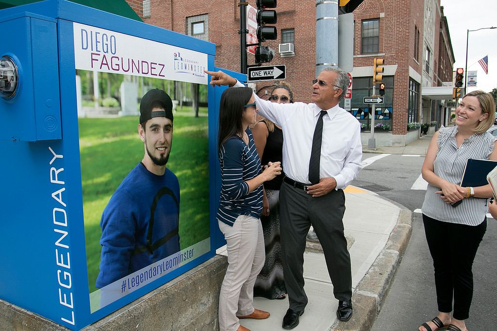 . Mayor Dean Mazzarella talk on Tuesday, July 16, 2019 about the City rebranding itself. Mazzarella, center, stands next to one of the five new legendary people signs that they have put up aound the city to show off some of the people that make Leominster Leominster with, from left, Small Business Coordinator Melissa Tasca, Diana Richard the mayors Aid and Nikki Peters the economic development coordinator for the city. This one is of new England Revolution player Diego Fagundez is located on main Street. SENTINEL & ENTERPRISE/JOHN LOVE