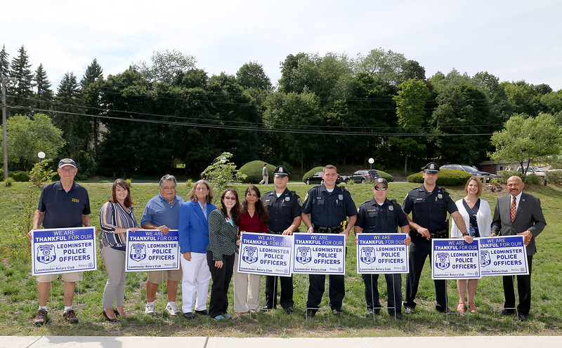 "The Leominster Rotary Club has made up some ""Thank You"" lawn signs for anyone that want to support the local police. From left, with the signs, is Rotary members Frank Ardinger, Nikki Paglieroni, John Souza, Past President Claire Freda, Club President Jennifer Stacy, Bharti Bhakta, with police officers Michael Booth, Eric Craig, John Bouchard and Billy Taylor. On the right is Rotary members Mary Dean and Victor Bhakta. SENTINEL & ENTERPRISE/JOHN LOVE"