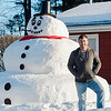 Lee Kosiewski stands next to a snowman he built outside his Ringer Street home in Leominster on Friday, February 17, 2017. SENTINEL & ENTERPRISE / Ashley Green