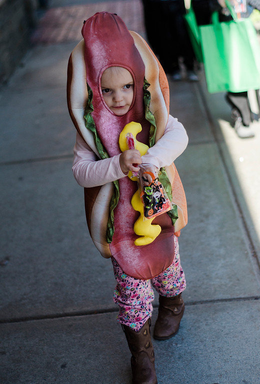 . Quinn McGrath, 3, investigates her candy stash during the Leominster trick-or-treating on Saturday, October 21, 2017. SENTINEL & ENTERPRISE / Ashley Green