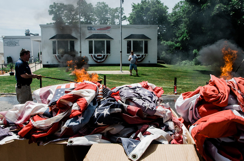 Volunteers gathered at the Leominster Veterans Memorial Center on Wednesday, June 14, 2017, Flag Day, to properly dispose of tattered flags by burning them in a fire pit. SENTINEL & ENTERPRISE/ Ashley Green
