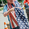 Bob Haskell drapes flags around his neck to prevent them from touching the ground while volunteers gather at the Leominster Veterans Memorial Center on Wednesday, June 14, 2017, Flag Day, to properly dispose of tattered flags by burning them in a fire pit. SENTINEL & ENTERPRISE/ Ashley Green