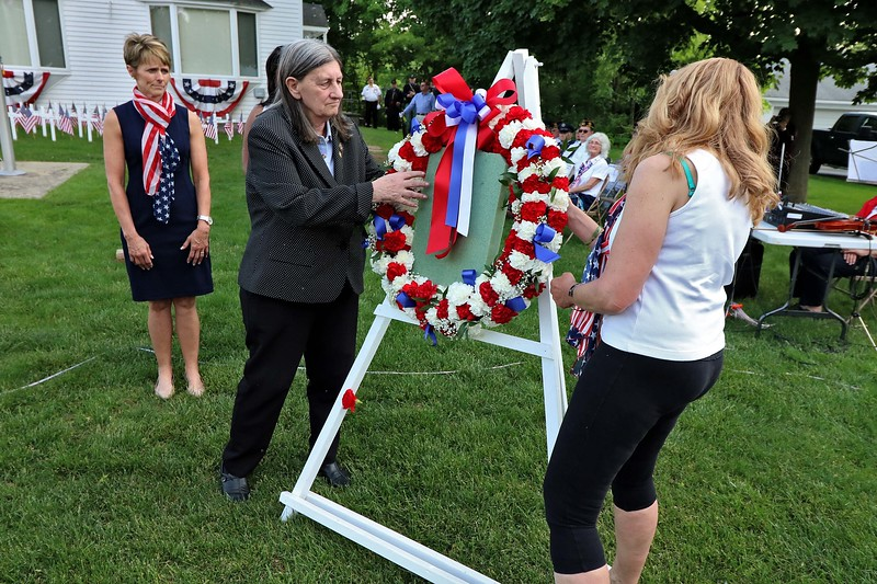 The White Cross Twilight Memorial Service was held at in front of the Leominster Veterans' Center on Friday night May 25, 2018. Each white cross represents a service member from Leominster that is missing-in-action, lost-at-sea, buried at sea or buried on foreign soil. Their remains have never returned home. Gold Star Mother Pauline Roberge, on right, and Gold Star wife Claire Freda place a memorial wreath during the ceremony. SENTINEL & ENTERPRISE/JOHN LOVE