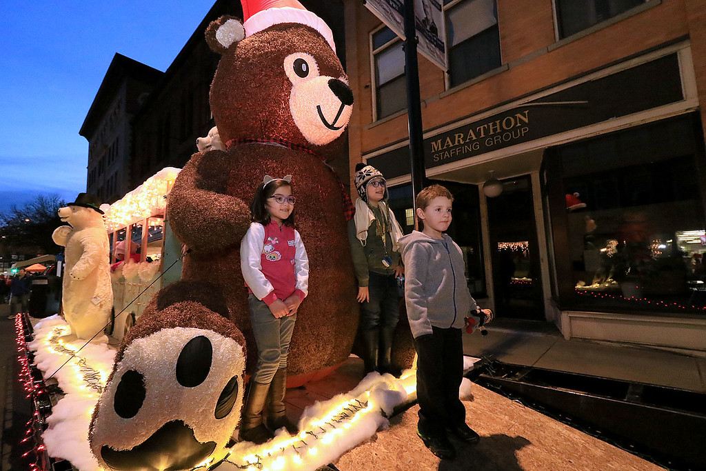 . The 13th Annual Leominster Holiday Stroll was held on on Saturday, December 1, 2018 in Downtown. Ivy Rose, 5, Memphis Rose, 8, and Nicholas Uphold, 4, of Leominster pose for a picture next to a a big bear on the Polar Express  float on main street during the stroll. SENTINEL & ENTERPRISE/JOHN LOVE