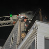 Fire 199 Prospect St Leominster - Here Ff Brandon O'Connor gets ready to drop the propane tank from the 2nd floor of the dwelling. SENTINEL&ENTERPRISE/Scott LaPrade