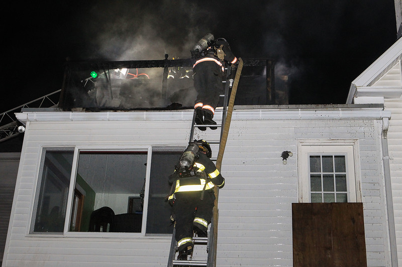 Firefighters take a line up over a ground ladder SENTINEL&ENTERPRISE/Scott LaPrade