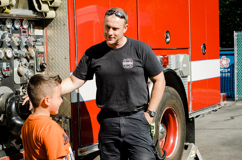 Firefighter Dave Fagon chats with Juan Ruiz, 9,  in front of one of the Leominster Fire Department trucks during the National Night Out event held at Watermill Apartments on Tuesday, August 1, 2017. SENTINEL & ENTEPRISE / Ashley Green