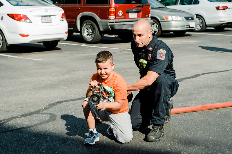 Lt. Jeff Vaillette helps Juan Ruiz, 9, test out a hose off one of the Leominster Fire Department trucks during the National Night Out event held at Watermill Apartments on Tuesday, August 1, 2017. SENTINEL & ENTEPRISE / Ashley Green