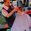 Luis Feliciano, of Brothers Barbershop, cuts the hair of Anthony Wheller during the National Night Out event held at Lowe Park in Fitchburg on Tuesday, August 1, 2017. SENTINEL & ENTERPRISE / Ashley Green