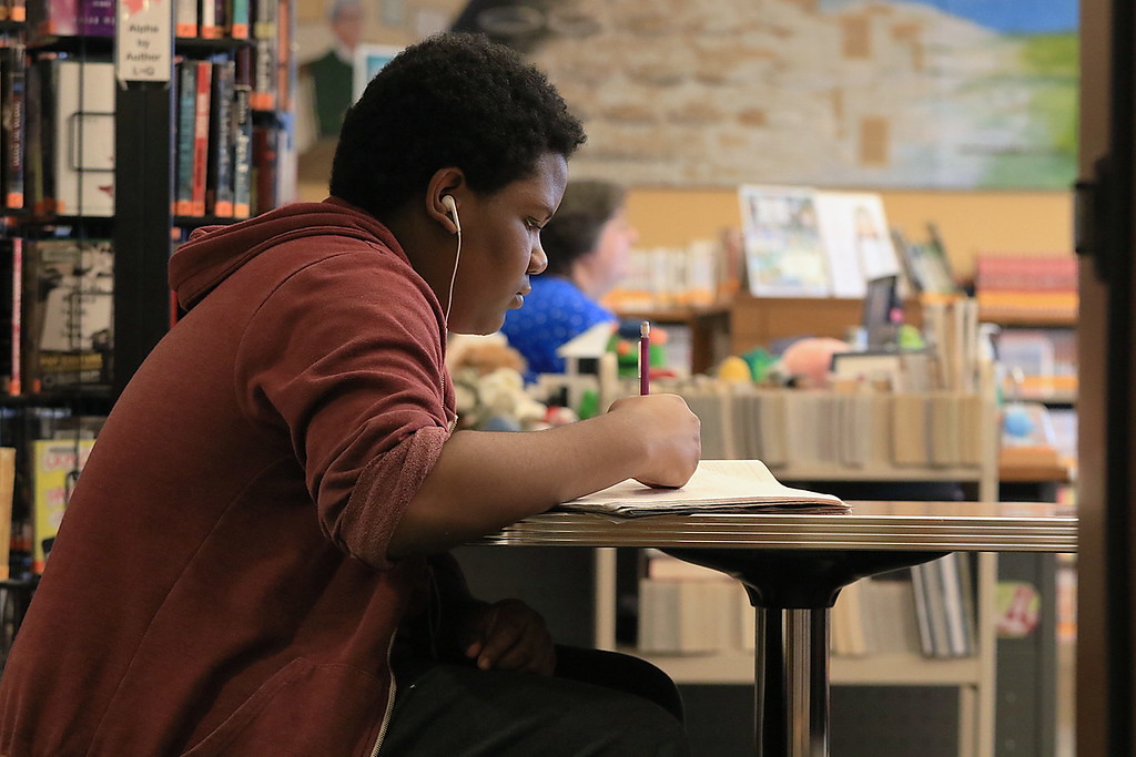 . Frederick Auguste, 13, does his eighth grade math homework while hanging out in the Leominster Public Library\'s teen room on Tuesday afternoon. SENTINEL & ENTERPRISE/JOHN LOVE