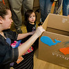 Tatiana Lara helps Elissha, 2, decorate her cardboard car during the drive-in movie at Leominster City Hall on Thursday, February 23, 2017. Children were able to come in and design their own box car and enjoy pizza and snacks while watching 'Zootopia' on a large projector screen. SENTINEL & ENTERPRISE / Ashley Green