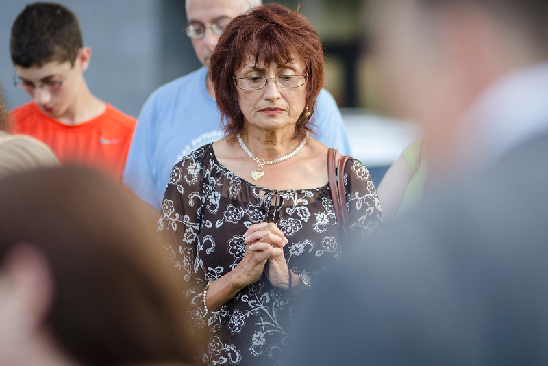 Mary Brooks, of Fitchburg, bows her head in prayer during the vigil in memory of Leominster-born Vanessa Marcotte. Worcester County District Attorney Joseph Early Jr. confirmed during a press conference on Monday that the body of missing jogger and former Leominster resident Marcotte, 27, had been found in Princeton and that her death is being investigated as a homicide. SENTINEL & ENTERPRISE / Ashley Green
