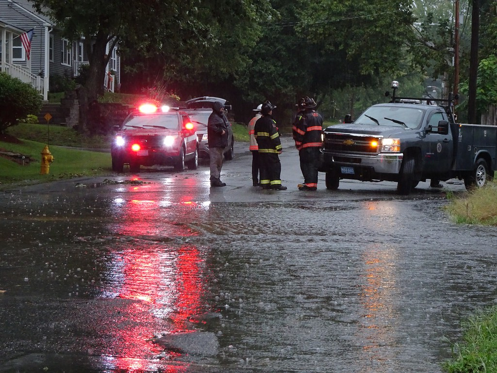 . Firefighters and public works officials at the corner of Burrage Avenue and Mascoma Street in Leominster on Tuesday. SENTINEL & ENTERPRISE/ PETER JASINSKI