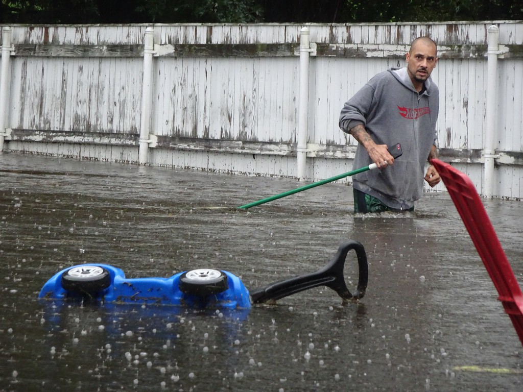. Issac Leon of 33 Burrage Ave. in Leominster wades through the small pond that was once his backyard after Tuesday\'s rainfall flooded his neighborhood. SENTINEL & ENTERPRISE / PETER JASINSKI