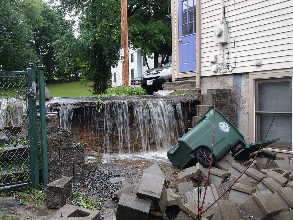 . A small waterfall that formed at this home at 3 Mascoma St., Leominster on Tuesday as floodwaters swept across Burrage Avenue.  SENTINEL & ENTERPRISE / PETER JASINSKI