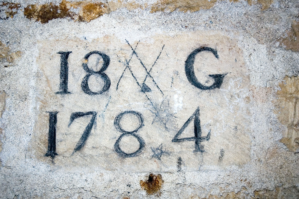 Here is how to read this : <br /> 18 is the number of the corridor<br /> G is the letter that identified the architect that suppervised the work<br /> and 1784 is the year the work was done<br /> easy isn't it ? ;)