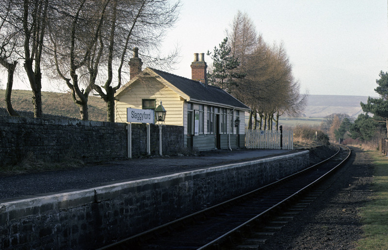 Slaggyford station, looking towards Haltwhistle, 28 February 1976     Eight and a half miles from Haltwhistle, and another example of a 1960s nameboard next to an oil lamp! Photo by Les Tindall.