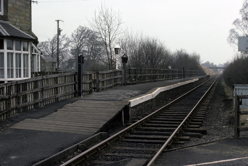 Featherstone station, looking towards Alston, 28 February 1976      Three miles from Haltwhistle.  Beyond the platform a family can just be seen walking alongside the track, away from the camera. Photo by Les Tindall.