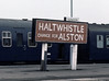 Station name board, Haltwhistle, 28 February 1976     The soon to be redundant nameboard is in North Eastern Region tangerine.  E50199 is a Metro-Cammell class 101 DMBS Photo by Les Tindall.