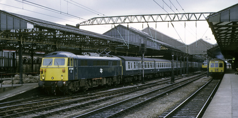 87026, Crewe, 14 July 1974.  The 87, which was two months old, sets off with the 1900 Liverpool - Euston.  At right is the 1802 Llandudno - Stoke DMU.  NB the pile of mailbags on the platform by 87026.  It was withdrawn in 2006 and exported to Bulgaria.  Photo by Les Tindall.