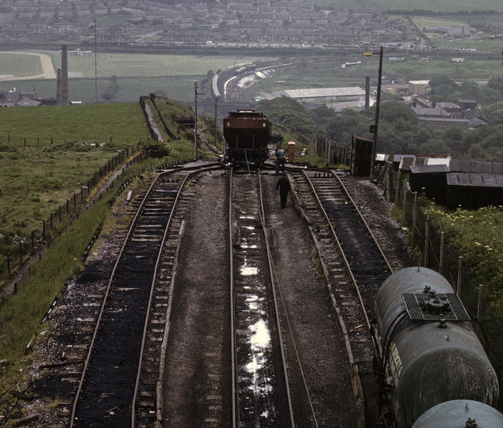 Corkickle Brake, Whitehaven, 9 June 1973.  This rope-worked incline was built in 1881, but fell into disuse between the wars.  It was rebuilt in 1955 to serve the Marchon (later Albright & Wilson) chemical works next to the Ladysmith washery.  The top of the Brake was 250 ft higher than the bottom.  This view looks east over the incline, down which wagons are being lowered.  More wagons can be seen at its foot in the distance, and beyond them are wagons on the former Furness Rly line from Barrow.  In 1964 the Brake was handling over 500,000 tons a year, but it closed in 1986.  Photo by Les Tindall.