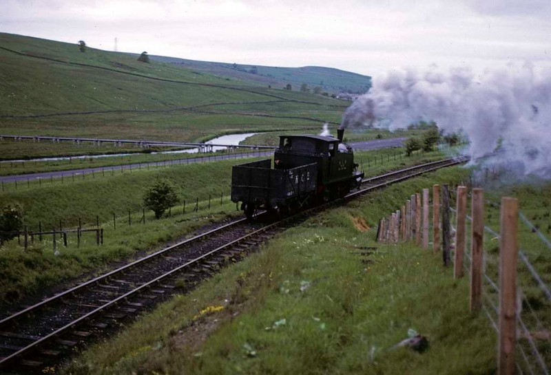 National Coal Board West Ayr Area 0-6-0T No 24, Waterside, June 1973. Barclay 2335 / 1955 runs light from Dunaskin to Minnivey colliery in the early morning.  There is a man in the makeshift tender, whch all Waterside locos had.  Photo by Les Tindall.
