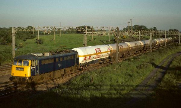 85006, Great Bridgeford, August 1977.  Heading BOC tank wagons.  The loco became 85101 and is preserved. Photo by Les Tindall.