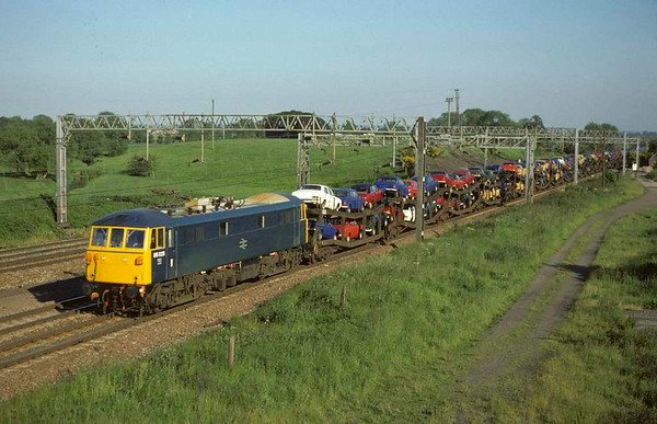 86025, Great Bridgeford, August 1977.  Heading a train of British Leyland cars - Marinas and Maxis etc. The loco became 86425 and was scrapped in 2005. Photo by Les Tindall.