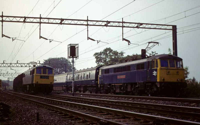86011 (left) & 86101 Sir William A Stanier FRS, Whitehouse Junction, June 1979.  86101 heads the 1618 Manchester - Euston past 86011, stopped at the signal with a freight.  86011 became 86611 and was scrapped in 2004.  86101 is preserved.  Photo by Les Tindall.