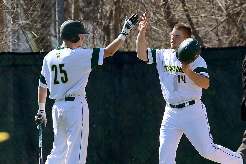 . Lesley University Baseball played Fitchburg State University on May 1, 2018. FSU\'s Sean Maki gets a high five from teammate Joshua Macomber after scoring a run during action in their game. SENTINEL & ENTERPRISE/JOHN LOVE