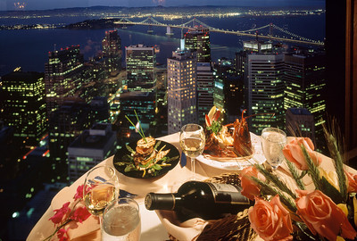 "Carnelian room overlooking the City By the Bay. Our food on the table lit by a number of tungsten mini spots balances with dusk and the lights of the City. This image was one exposure on a 4x5 transparency, pre Photoshop. That's why they call ihis time of day ""Magic Hour""."