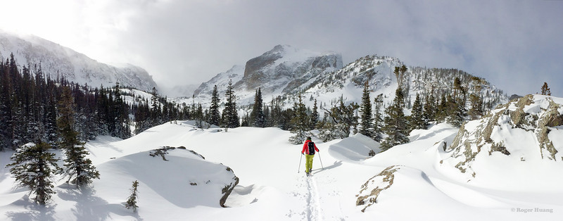 Panorama of Eli approaching Lake Haiyaha with Hallett Peak in the background.