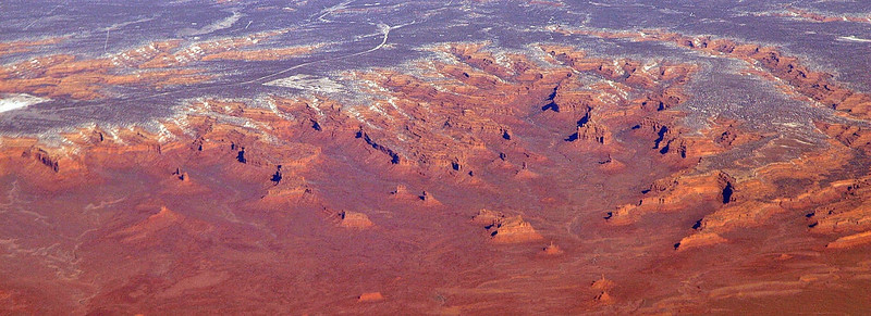 "An aerial photograph looking northwest into the Valley of the Gods. The 17-mile valley road winds through the open expanse of sagebrush and, in places, the many tall spires with interesting names in the center of this image (about half way along the valley road traveling in either direction, in the north part of the valley.) The Moki Dugway (see next image) is located at the extreme left edge of this image in the center (carved out of the side of Cedar Mesa, which the Moki Dugway ascends.) Cedar Mesa is in the upper portion of this image. <br /> <br /> This aerial photograph was taken on February 18, 2008 by ""Flickr"" member Doc Searls. Rights to this photo were released in part to Wikimedia Commons and the public domain. See Wikipedia and search for the Valley of the Gods for more information about this image."