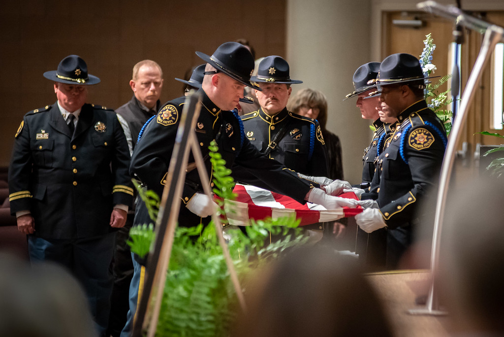 . Members of the Larimer County Sheriffs Department Honor Guard fold a flag during a memorial service for Lew Gaiter on Saturday morning at Timberline Church in Fort Collins.