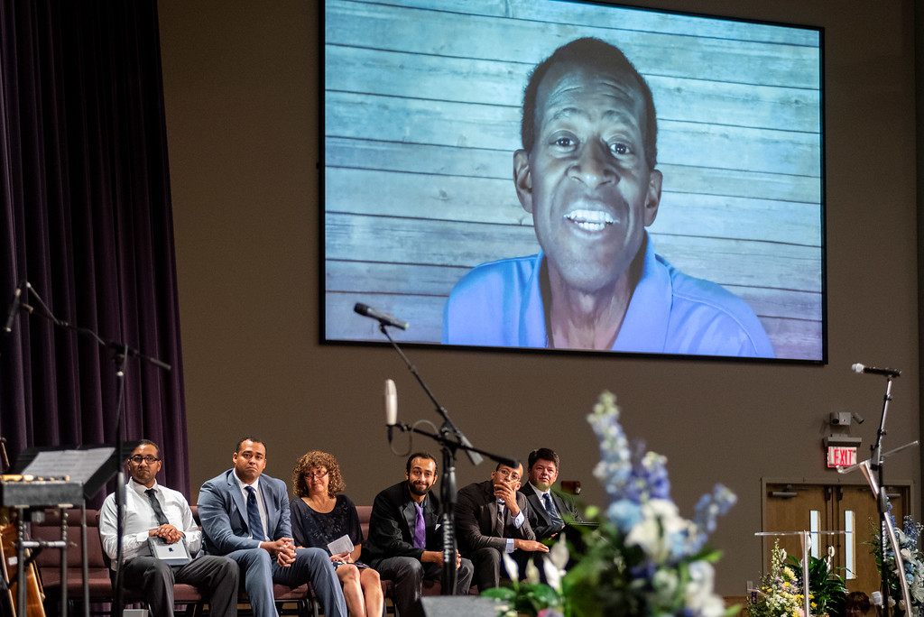 . A posthumous video message from Lew Gaiter plays during his memorial service on Saturday morning at Timberline Church in Fort Collins as his family, from left, son Josiah, son Jon, wife Jeanette, son Samuel, son Micah and pastor Matt Tarka watch.