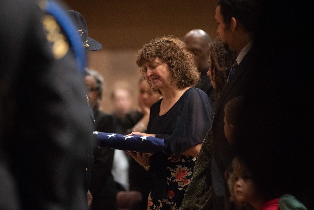. Members of the Larimer County Sheriffs Department Honor Guard present a flag to Jeanette Gaiter during a memorial service for her husband Lew Gaiter on Saturday morning at Timberline Church in Fort Collins.
