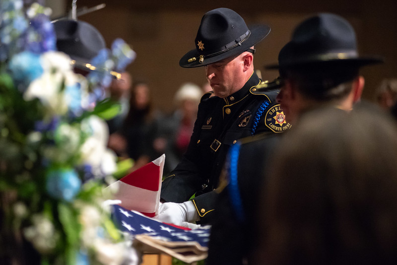 Members of the Larimer County Sheriffs Department Honor Guard fold a flag during a memorial service for Lew Gaiter on Saturday morning at Timberline Church in Fort Collins.