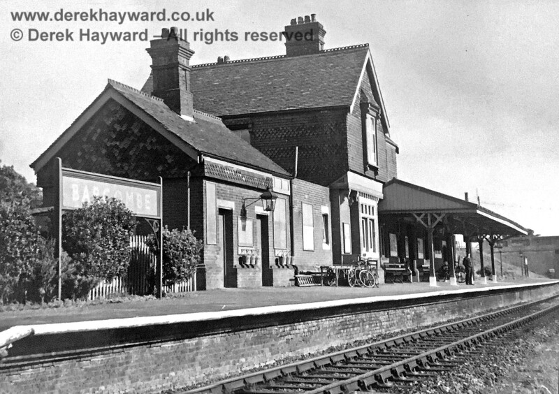 Brenda Barnes has kindly supplied this early image of Barcombe Station when it was still open to traffic.  A porter, hands in pockets, gazes north, there is a generous supply of fire buckets, and bicycles lean casually against platform furniture.  The date is unfortunately not recorded and the image has received some restoration.  Brenda Barnes retains all rights to this image.