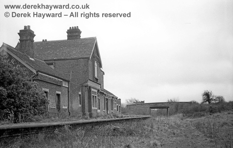 """I am grateful to John Attfield for allowing me to use some of his images in this gallery.  A very different scene after closure.  Barcombe Station captured on 12 April 1965 looking south, with the station building (then neglected) on the left.  In the distance the road bridge remained in use in it's original condition, but it was later classified as a """"Weak Bridge"""".  Attempts were initially made to strengthen it with tie rods, but at a later stage, in 2007,  it was infilled.  John retains all rights to this image."""