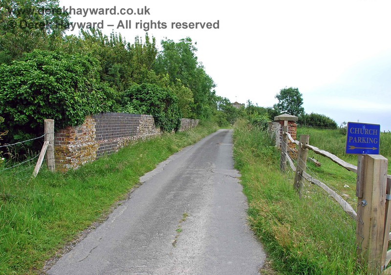 This view looks over the bridge to the south east.  The road leads only to a pleasant old church.  On the left the ground drops away in a sheer drop beyond the left hand parapet, but the trees prevent any view.