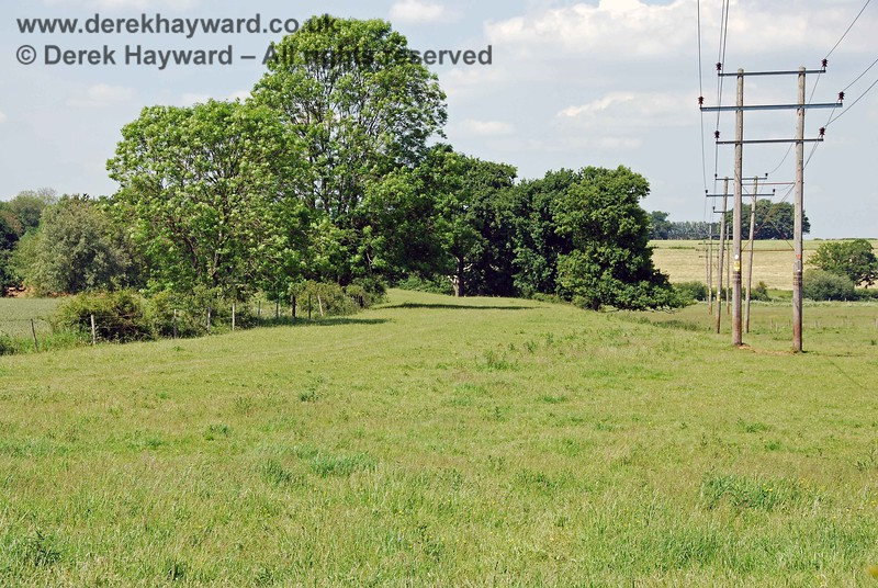 The well-maintained flat trackbed of the Sheffield Park line curved away between these trees, heading first for Barcombe.  Power lines follow the route for much of the way and make their first appearance here, but, at this point, they do not follow the route of the old line.