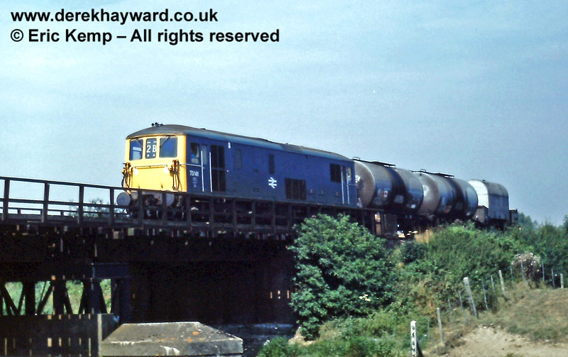 Outside Lewes on Thursday 13.08.1981.  Class 73 73141 is about to cross the River Ouse (on the bridge just north of the A27) with a freight train. The last wagon is a very unusual specialised transporter for DEMU engines (see next image).