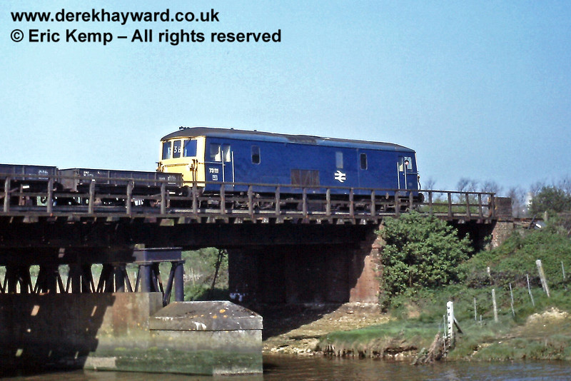 A member of the crew looks back at the photographer as Class 73 73111 crosses the River Ouse outside Lewes with a freight on  Wednesday 15.04.1981.