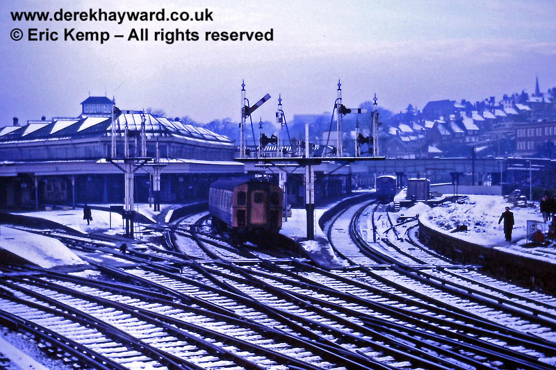 Viewed from the steps of the 'B' signal box, the eastern end of Lewes Station is seen in the snow on Friday 01.01.1971.  A train is leaving from the Down Main toward Hastings (Platform 2).  The platforms are arranged from Platform 1 on the right to Platform 8 on the left.  The two goods docks are on the right and there seems to be a puzzlingly large amount of pedestrian activity on the extreme right of the dock.
