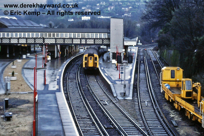 A wider view of Lewes Station on Saturday 09.01.1988.  Unit 1201, in blue and grey with Network South East logos, waits in the Up platform with a Brighton train.  The Up Loop siding is occupied with engineering stock.  On the left the old bi-directional double-sided Platforms 4/5 (Down Brighton Loop) have been filled in to platform level with ballast, and ornamental trees now stand where Uckfield line trains terminated.  On the left, nearest the camera, the platform has been extended.   Note the red painted lamps on the platforms, then a feature of Network South East stations.