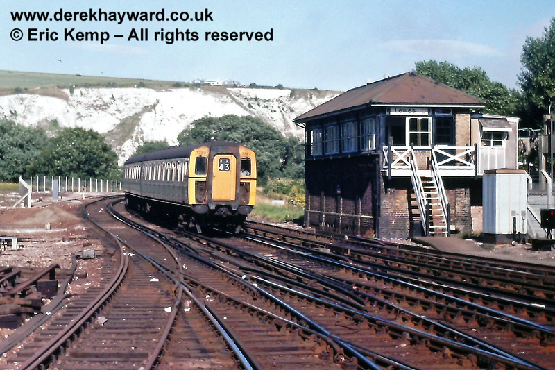 With the high chalk hills (Malling Hill) in the background,  4-VEP 7782 passes Lewes 'B' signal box with a Brighton train. A new fence stands on the left where the closed line to Uckfield used to diverge to the north.  Saturday 28.07.1979.