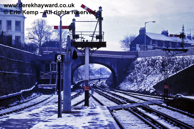 The view towards Brighton from the south western end of Lewes Station, with 'D' signal box on the left. A worker is walking towards Brighton beyond the bridge; high visibility clothing was not widely used at the time.  01.01.1971