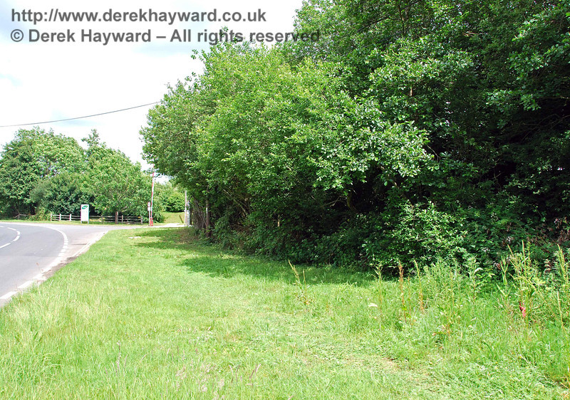Still looking north, a closer view of the southern embankment, but it is completely concealed by trees.  In the distance is the entrance to a former dairy.