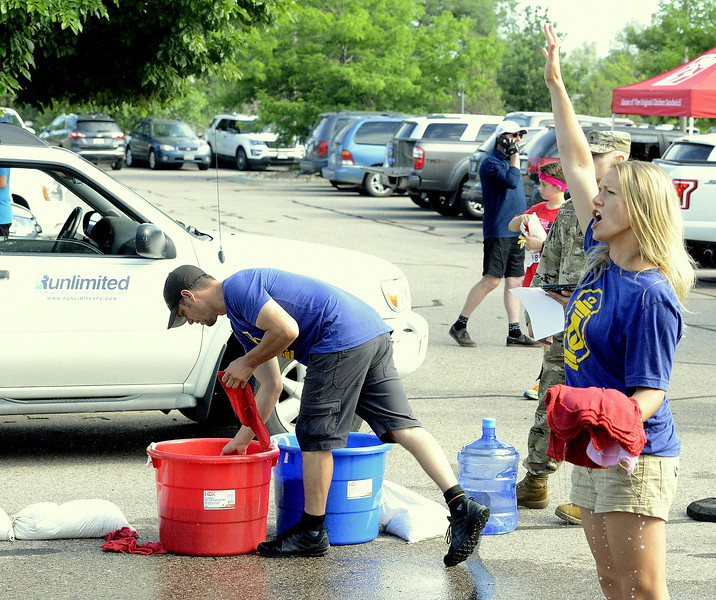 Michelle Bramlett and her husband Scott distribuited cold, wet towels to the finishers of Wednesday's Liberty 5K at Fairgrounds Park. (Mike Brohard/Loveland Reporter-Herald)