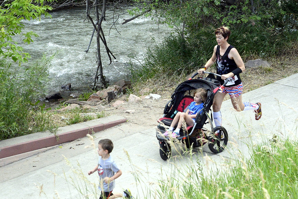 . Dena Sanders runs while she pushes a stroller along the path by the river during Wednesday\'s Liberty 5K at Fairgrounds Park. (Mike Brohard/Loveland Reporter-Herald)